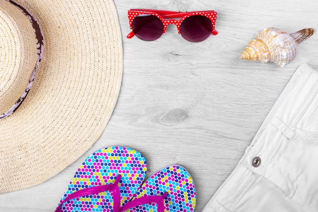 Straw beach woman's hat zonnebril top view seashell shorts slippers met ruimte voor tekst.
