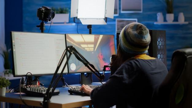 Streamer komt in de speelkamer en speelt videogames en praat met teamgenoten over het streamen van open chat en microfoon, en controleert de geluidsmixer. cyberprestaties op krachtige professionele computerapparatuur