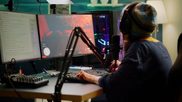 Streamer speelt fps-videogames en praat met teamgenoten over het streamen van open chat met professionele microfoon. cyber presteert in online toernooi op krachtige rgb-computer in gaming-studio