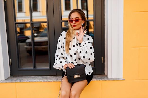 Street fashion look. sierlijke blonde dame in witte blouse en zwarte rok staande op geel.