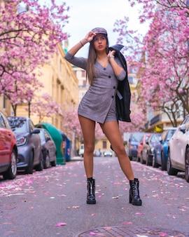 Street style in de stad, brunette blank meisje met leren jas wandelen in de stad met de bloeiende bomen in het voorjaar