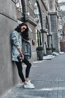 Street style. volledige lengte van mooie jonge vrouw in spijkerjasje die hand in haar houdt