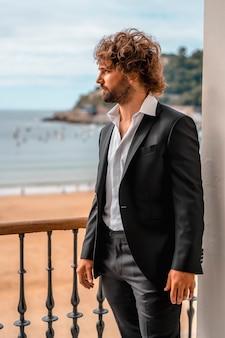 Streetstyle met een jonge brunette blanke man in een zwart pak en een wit overhemd in een luxe hotel, mode-editorial. model zat op het raam met uitzicht op zee