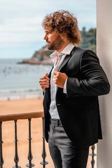 Streetstyle met een jonge brunette blanke man in een zwart pak en een wit overhemd in een luxe hotel, mode-editorial. model zat op het raam