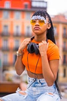 Streetstyle van een jonge trapdanseres met vlechten. ze poseert van het zwarte slijpende meisje van de afrikaanse etnische groep met een oranje shirt en een cowboybroek. met oranje huizenachtergrond