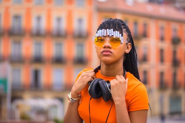 Streetstyle van een jonge trapdanseres met vlechten. ze poseert van het zwarte slijpende meisje van de afrikaanse etnische groep met zittend t-shirt, oranje zonnebril en cowboybroek. met oranje huizenachtergrond