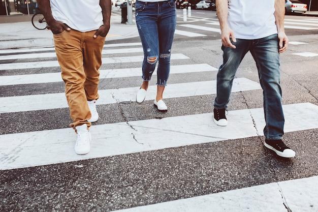 Streetwear kleding jeans mannen en vrouwen die de weg oversteken in de stad