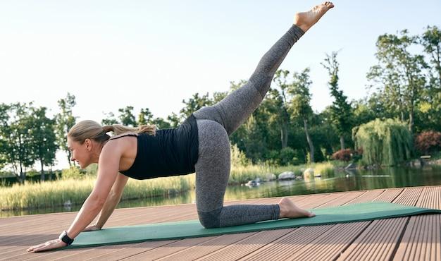 Strek en ontspan mooie ontspannen vrouw van middelbare leeftijd die in yoga pose staat met één been opgetild