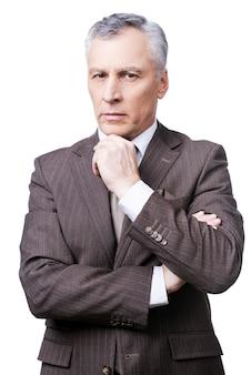 Strenge blik van directeur. doordachte volwassen man in formalwear die de hand op de kin houdt en naar de camera kijkt terwijl hij tegen een witte achtergrond staat