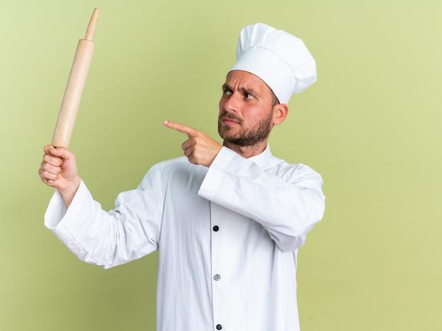 Strenge jonge blanke mannelijke kok in chef-kok uniform en pet met kijken en wijzend op deegroller geïsoleerd op olijfgroene muur