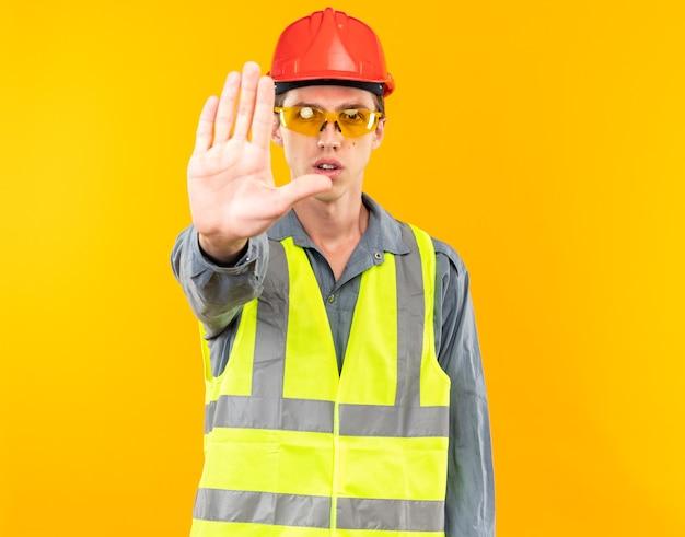 Strenge jonge bouwer man in uniform dragen van een bril met stop gebaar geïsoleerd op gele muur