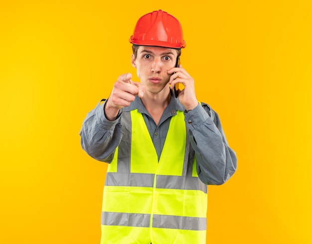 Strenge jonge bouwer man in uniform spreekt op telefoonpunten op camera