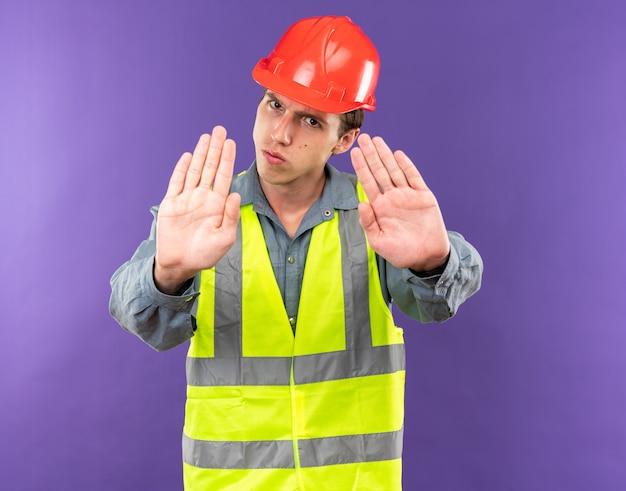 Strenge jonge bouwer man in uniform weergegeven: stop gebaar geïsoleerd op blauwe muur