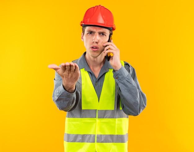Strenge jonge bouwman in uniform spreekt aan de telefoon en steekt zijn hand uit naar de camera