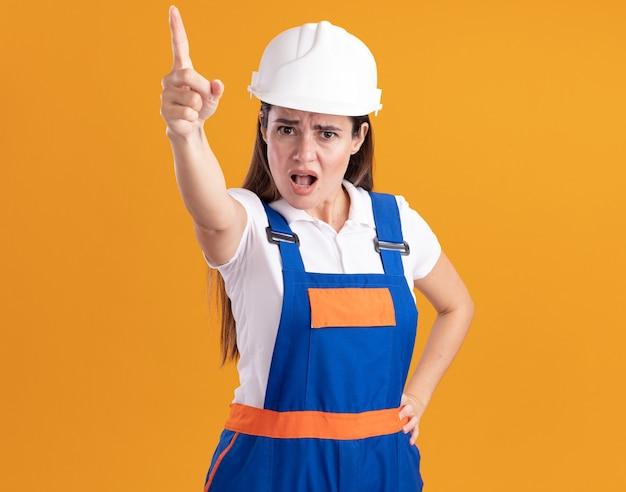 Strenge jonge bouwvrouw in uniform wijst op camera die hand op heup zet geïsoleerd op oranje muur