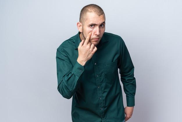 Strenge jonge knappe kerel die een groen overhemd draagt dat oogleden trekt