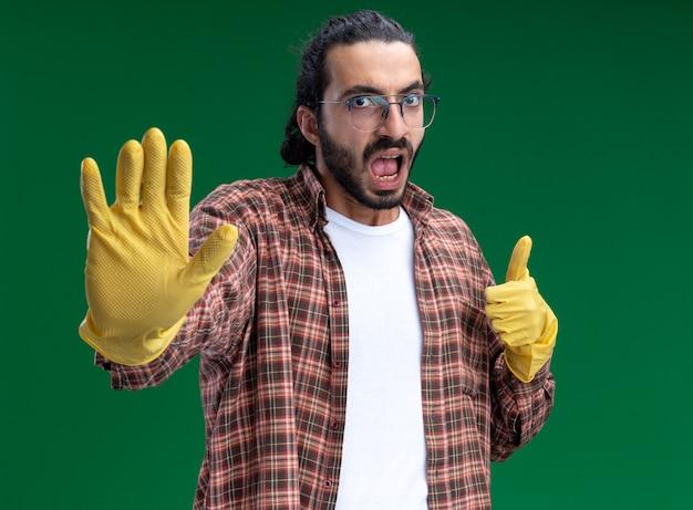 Strenge jonge knappe schoonmaakster die een t-shirt en handschoenen draagt met zijn duim omhoog en een stopgebaar laat zien dat op een groene muur is geïsoleerd