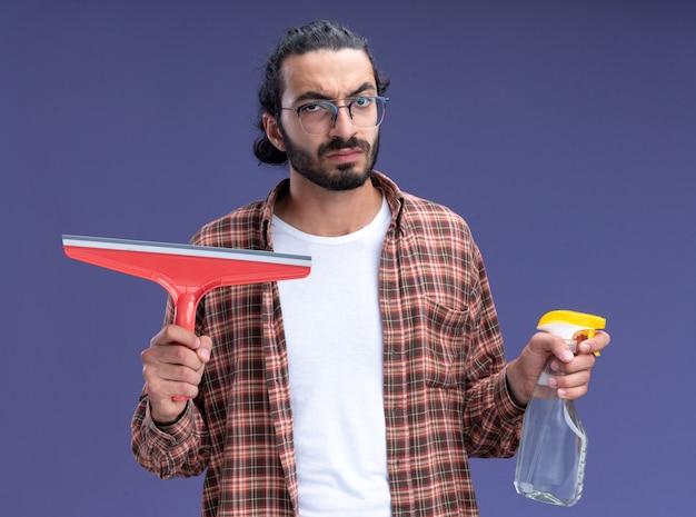 Strenge jonge knappe schoonmaakster met een t-shirt met een dweilkop met een spuitfles geïsoleerd op een blauwe muur
