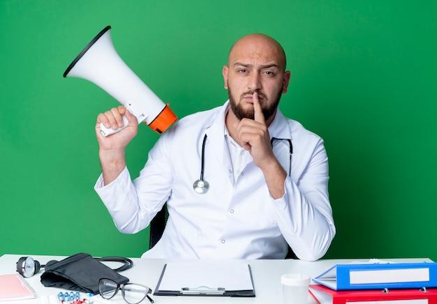 Strenge jonge mannelijke arts met een medisch gewaad en een stethoscoop die aan het bureau zit