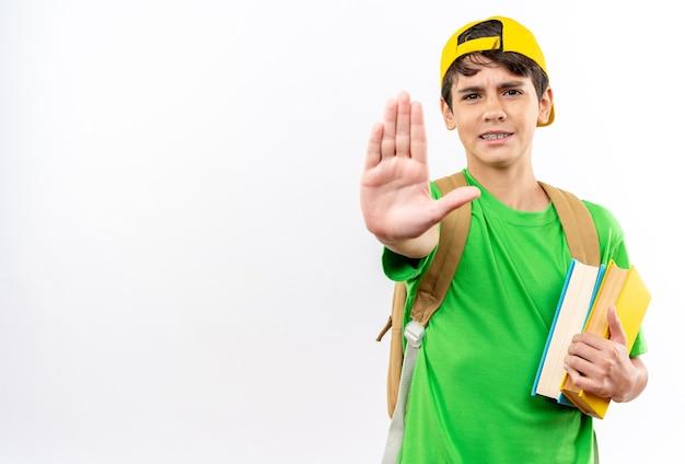 Strenge jonge schooljongen die een rugzak draagt met een pet die boeken vasthoudt die een stopgebaar tonen