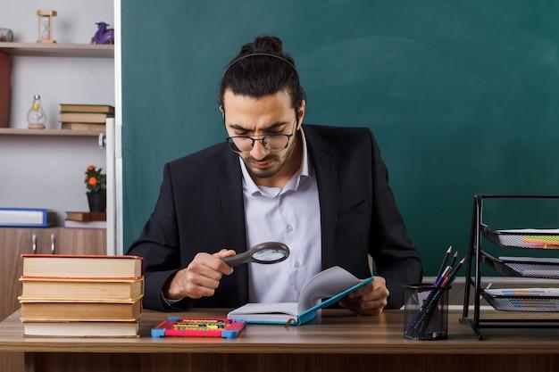 Strenge mannelijke leraar met een bril die een boek vasthoudt en leest met een vergrootglas aan tafel met schoolhulpmiddelen in de klas