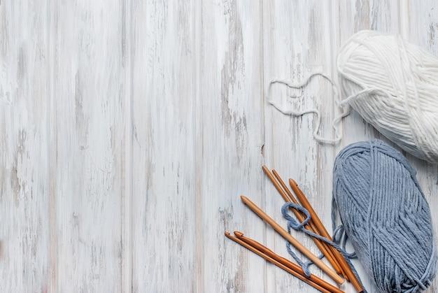Strengen van garen en haken voor het breien op een houten tafel.