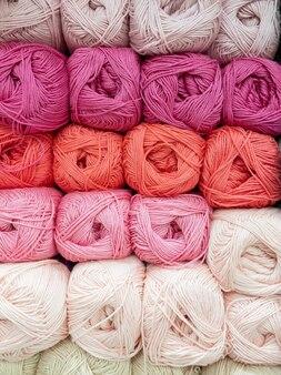 Strengen van rode en roze draad voor handwerk close-up. achtergrondafbeelding, naaien, borduren, handgemaakt, hobby, diy concept.