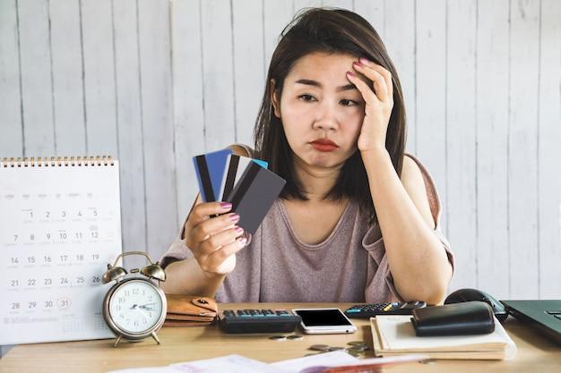 Stress aziatische vrouw creditcards in de hand te kijken