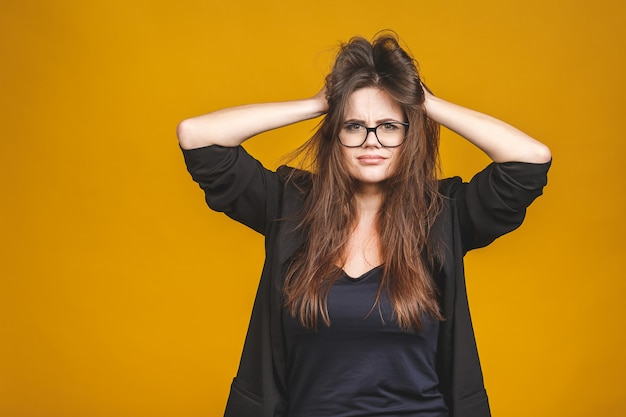 Stress concept. een zeer gefrustreerd en boos zakenvrouw trekt haar haren. geïsoleerd tegen geel.