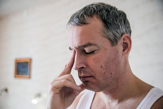 Stress, hoofdpijn, wanhoop, verdriet en mensenconcept. gefrustreerde jonge man die zijn neus masseert en de ogen dicht houdt. man voelt sterke hoofdpijn
