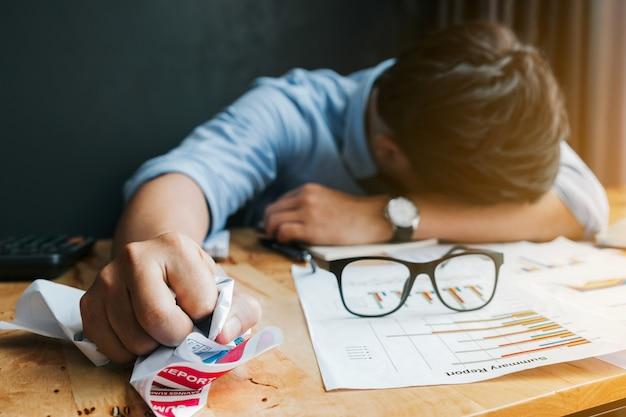 Stress of falen concept. angry en moe zakenman crumpling papieren in het kantoor.