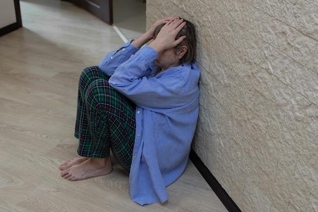 Stress senior vrouw zittend op de vloer met zijn gezicht in zijn handen.