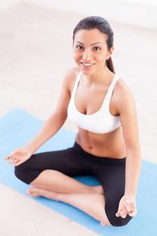 Stress wegnemen. bovenaanzicht van aantrekkelijke jonge indiase vrouw die in de lotuspositie zit en naar de camera glimlacht