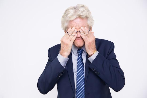 Stressed senior blanke zakenman wrijven ogen