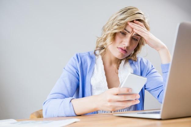 Stressed vrouw met behulp van mobiele telefoon