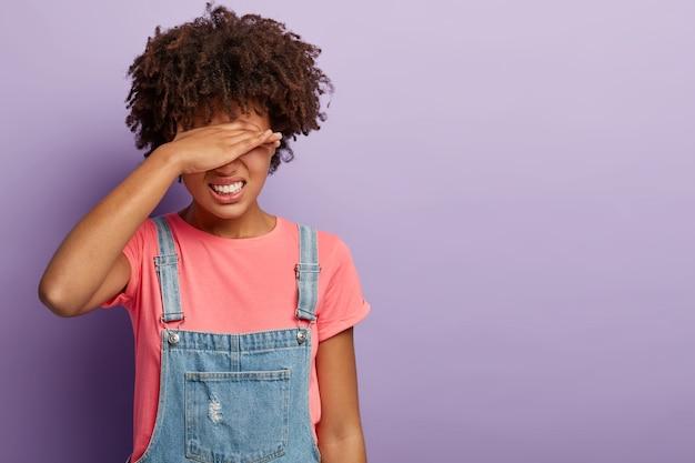 Stressvolle afro-amerikaanse vrouw bedekt ogen met hand, klemt tanden van pijn, lijdt aan hoofdpijn, voelt zich depressief, verbergt zichzelf