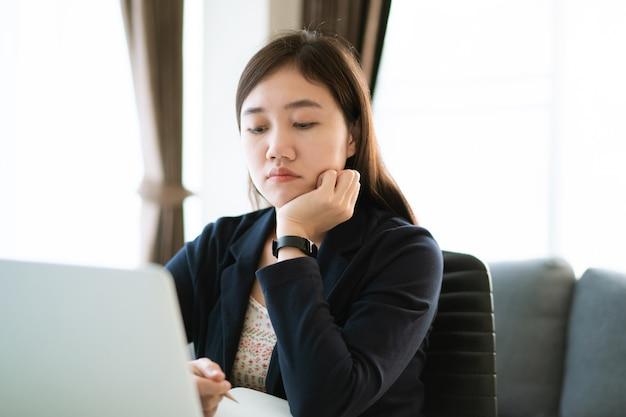 Stressvolle aziatische zakenvrouw die op kantoor werkt met lijden en ongelukkige emoties. vrouw voelt zich ongemakkelijk tijdens het werken op kantoor, vrouw lijdt onder haar werk. meisje bezorgd over overwerk.