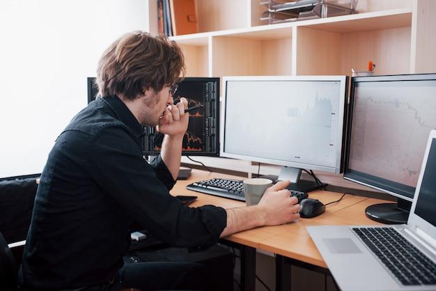 Stressvolle dag op kantoor. de jonge handen van de zakenmanholding op zijn gezicht terwijl het zitten bij het bureau in creatief bureau. beurs die forex financiën grafisch concept handel drijven