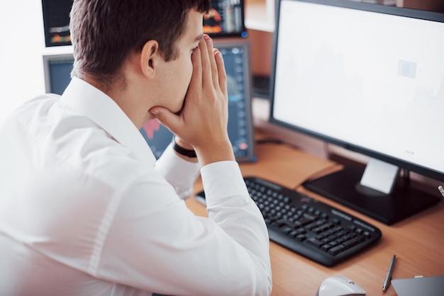 Stressvolle dag op kantoor. jonge zakenman hand in hand op zijn gezicht zittend aan het bureau in creatieve kantoor. beurs handel forex financiën grafisch concept.
