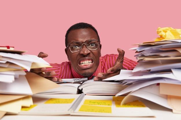Stressvolle geïrriteerde vermoeide leraar klemt tanden in woede, gebaart en kijkt direct, voelt vermoeidheid bij het voorbereiden op lessen of het maken van een project