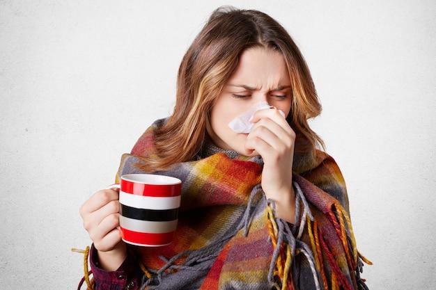 Stressvolle jonge mooie vrouw niest in servet, heeft lopende neus, drinkt warme drank, gewikkeld in plaid, lijdt aan kou, geïsoleerd over wit