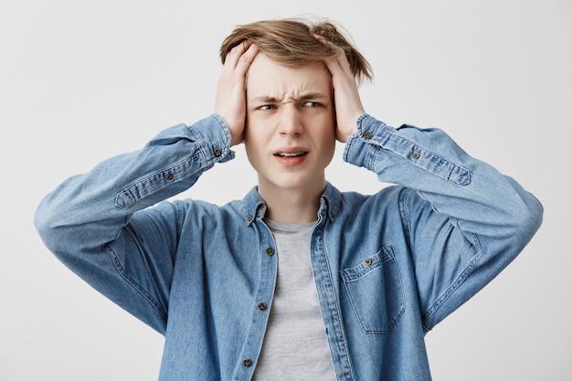 Stressvolle jongen met handen in blond haar heeft hoofdpijn, balt tanden met pijn, leeft in spanning en heeft veel problemen. mannelijke student lijdt aan pijn, heeft een vermoeide en uitgeputte uitdrukking