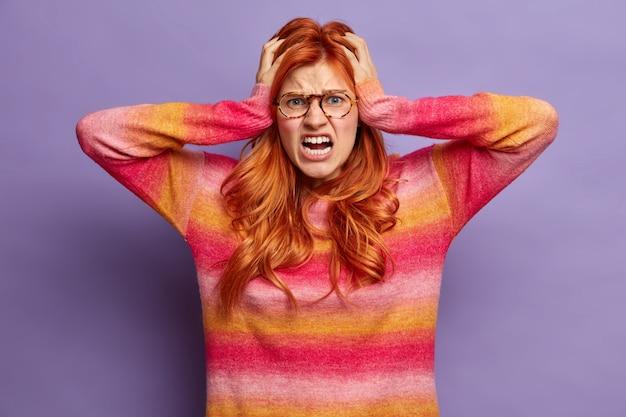 Stressvolle roodharige vrouw ziet er wanhopig uit en houdt met paniek de handen op het hoofd en geïrriteerd door verontrustend geluid, gekleed in een casual jumper, houdt luid haar mond wijd open. negatieve emoties
