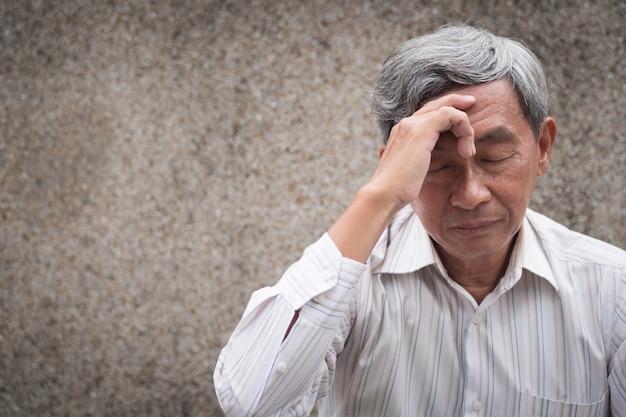 Stressvolle senior oude man die lijdt aan hoofdpijn