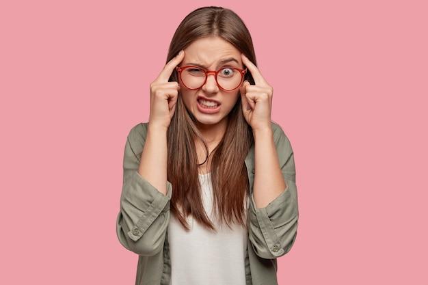 Stressvolle student poseren tegen de roze muur