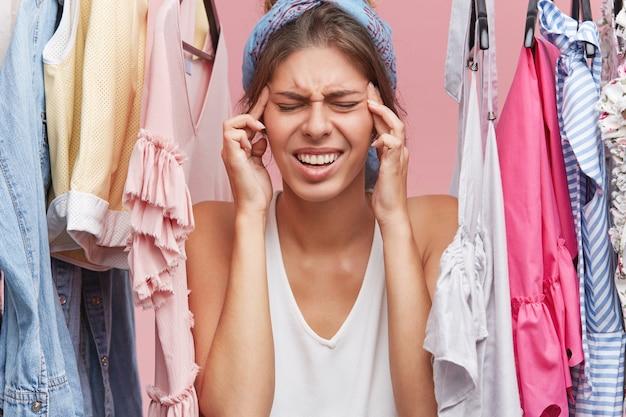 Stressvolle vrouw gaat huilen terwijl ze in de buurt van verschillende kleding staat, problemen heeft bij het beslissen wat ze moet dragen