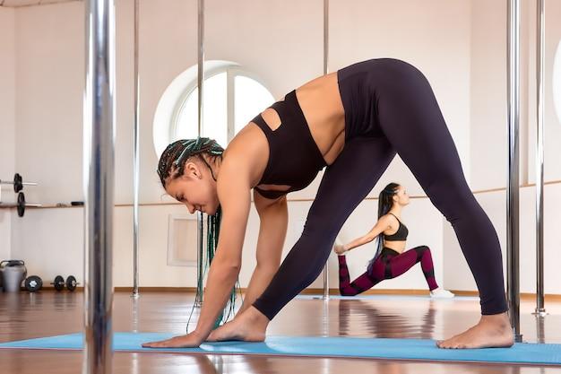 Stretchen in de sportschool voordat je aan yoga of paaldansen doet