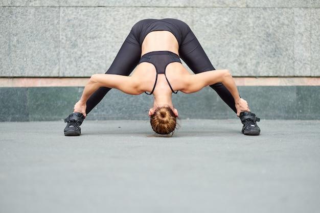 Stretching vrouw. fitness of turner of danser doen oefeningen op grijze muur