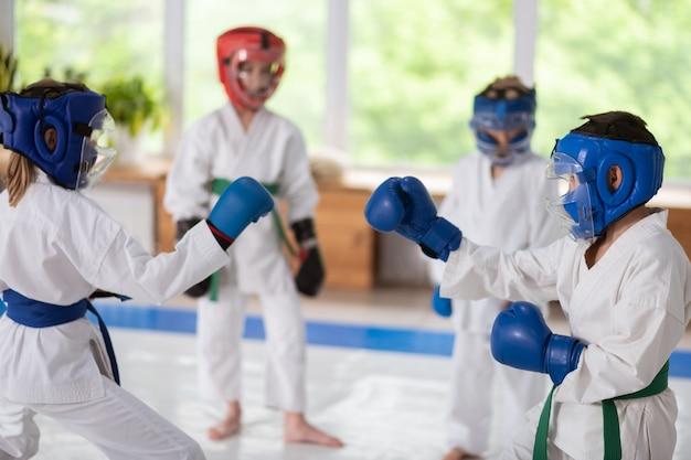 Strijd tijd. atletische sterke jongen en meisje in beschermende helmen en bokshandschoenen die vechten