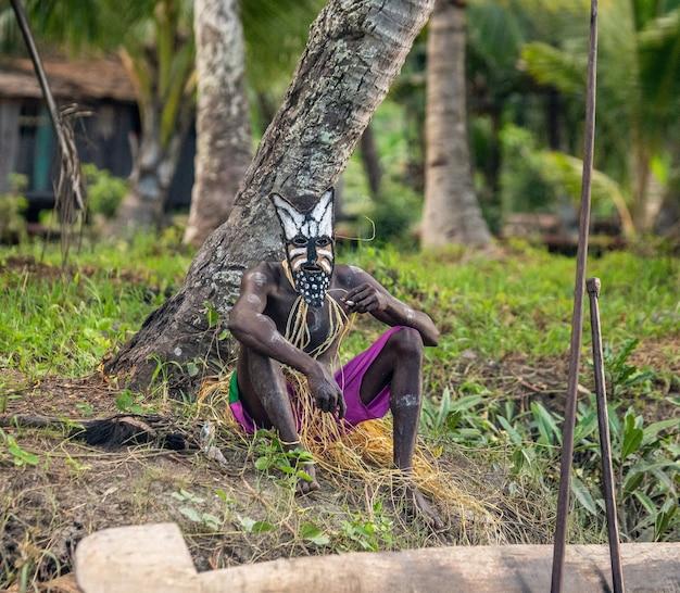 Strijder van de asmat-stam in een gevechtsmasker zit in de buurt van een boom.